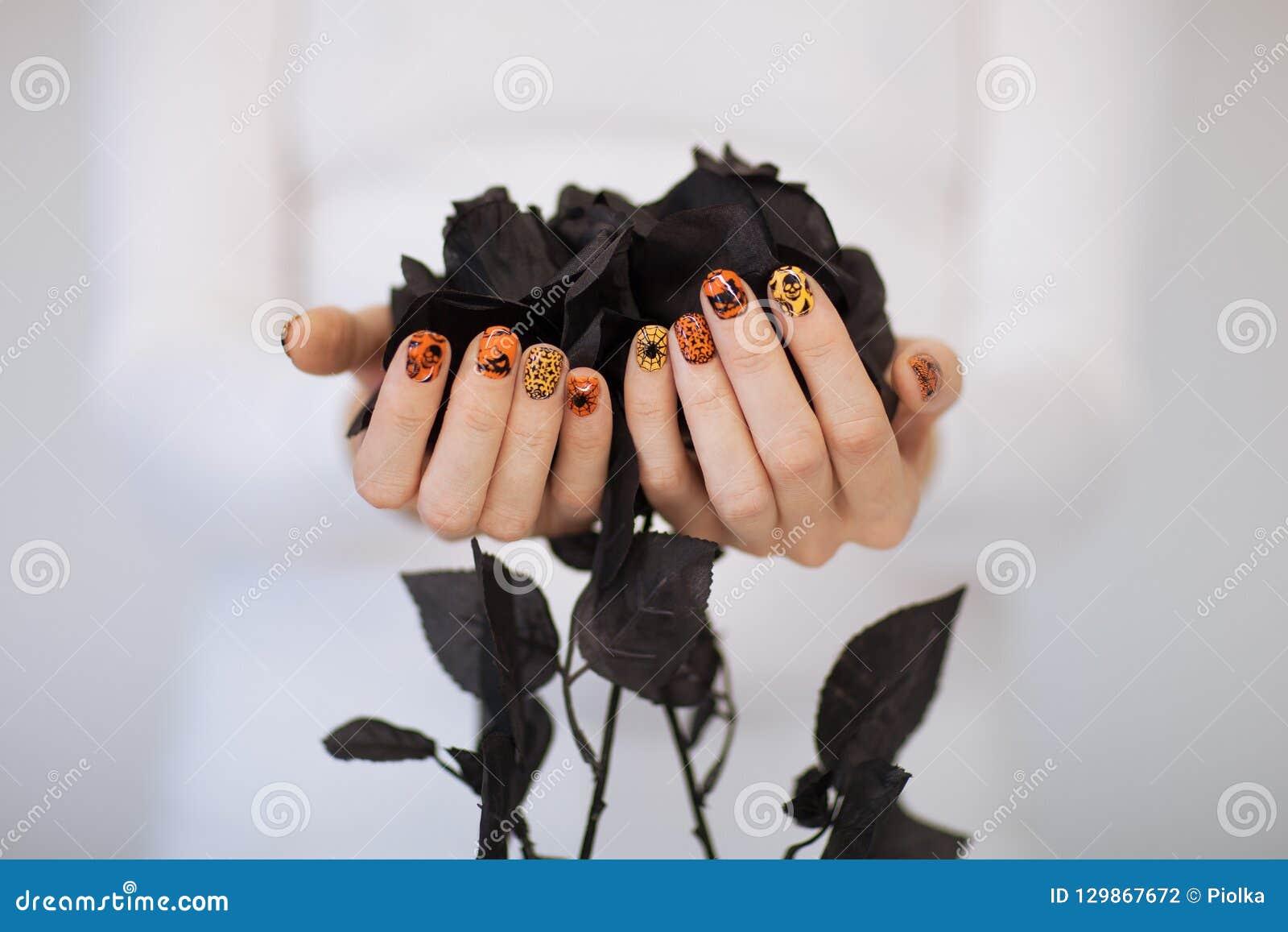Красивые руки женщины с милым маникюром хеллоуина держа черные розы