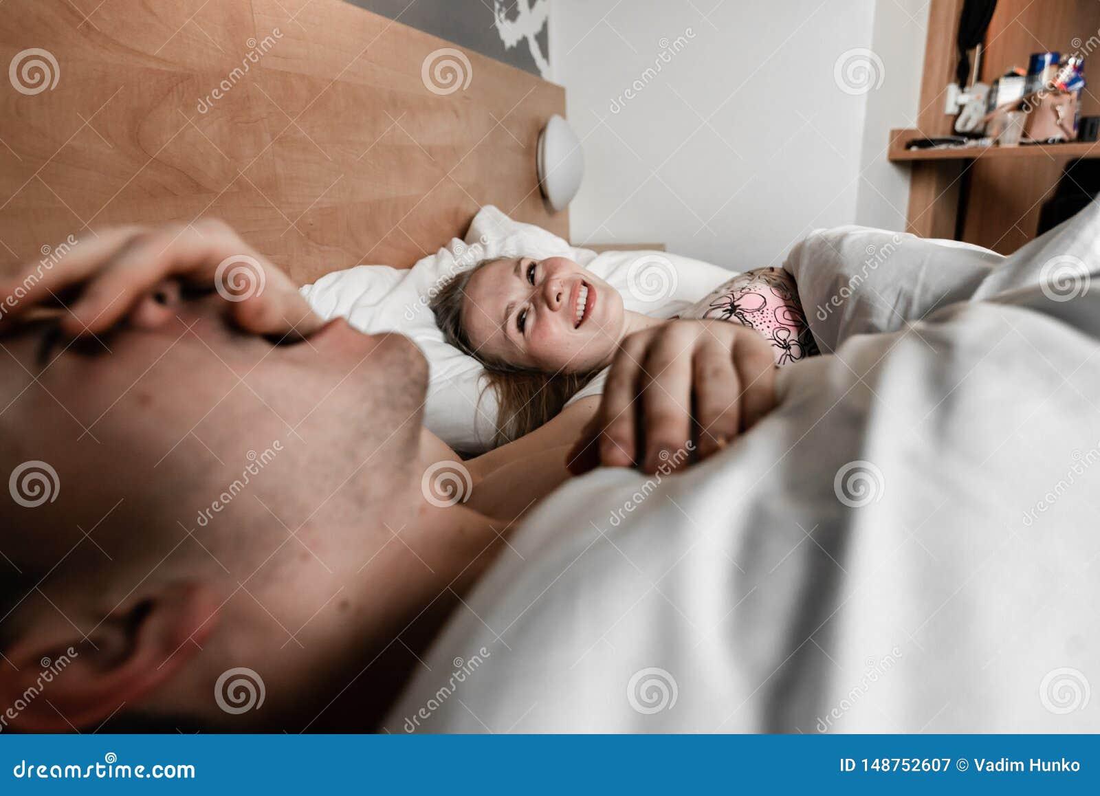 Красивые счастливые молодые пары или семья просыпая вверх совместно в кровати