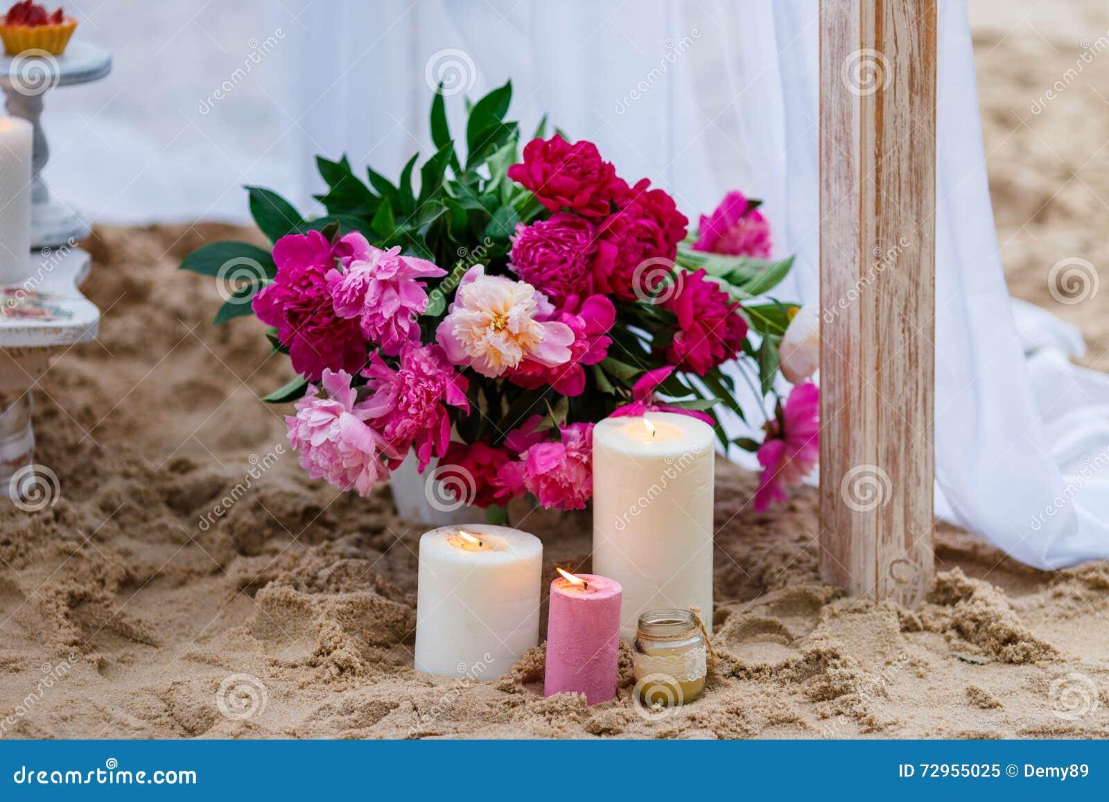 Красивые, чувствительные украшения свадьбы с свечами и свежие цветки на пляже