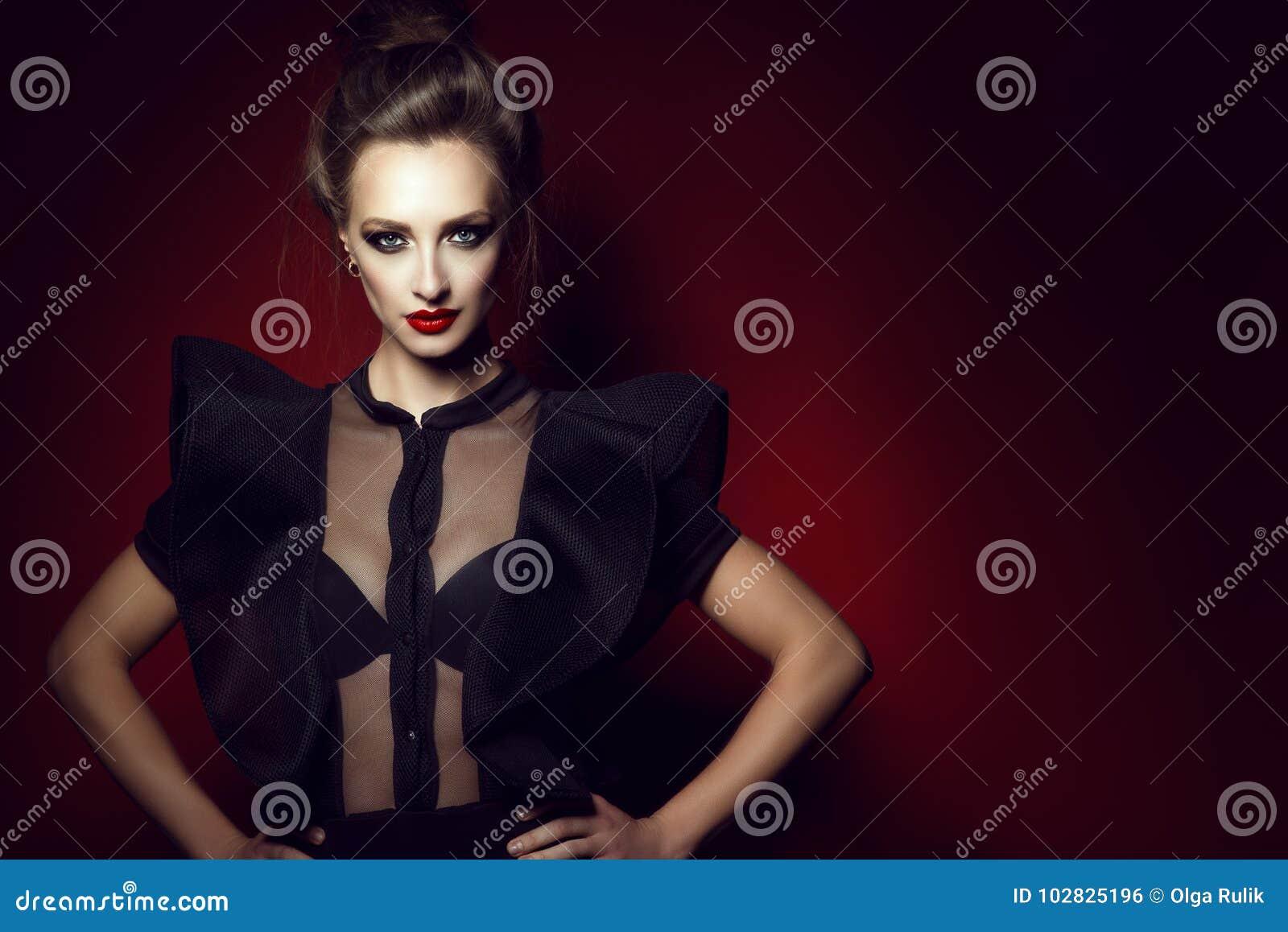 Красивые шикарная дама с волосами updo и совершенные составляют носить semi прозрачную блузку с рукавами оборки, ее руки шнурка н
