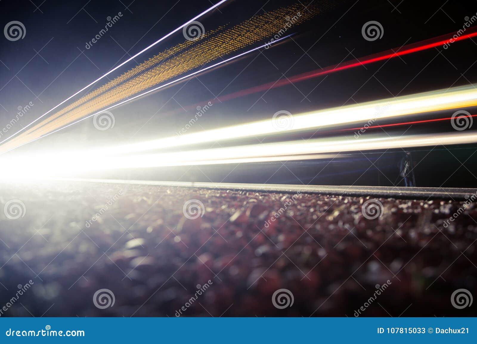 Красивый, абстрактный автомобиль освещает на проселочной дороге Торгуйте в ноче, смотря от обочины