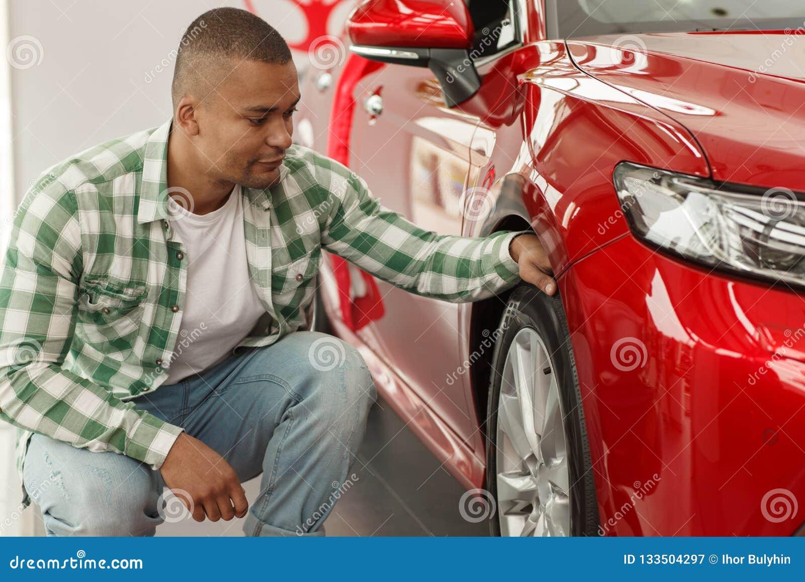 Красивый африканский человек выбирая новый автомобиль на дилерских полномочиях