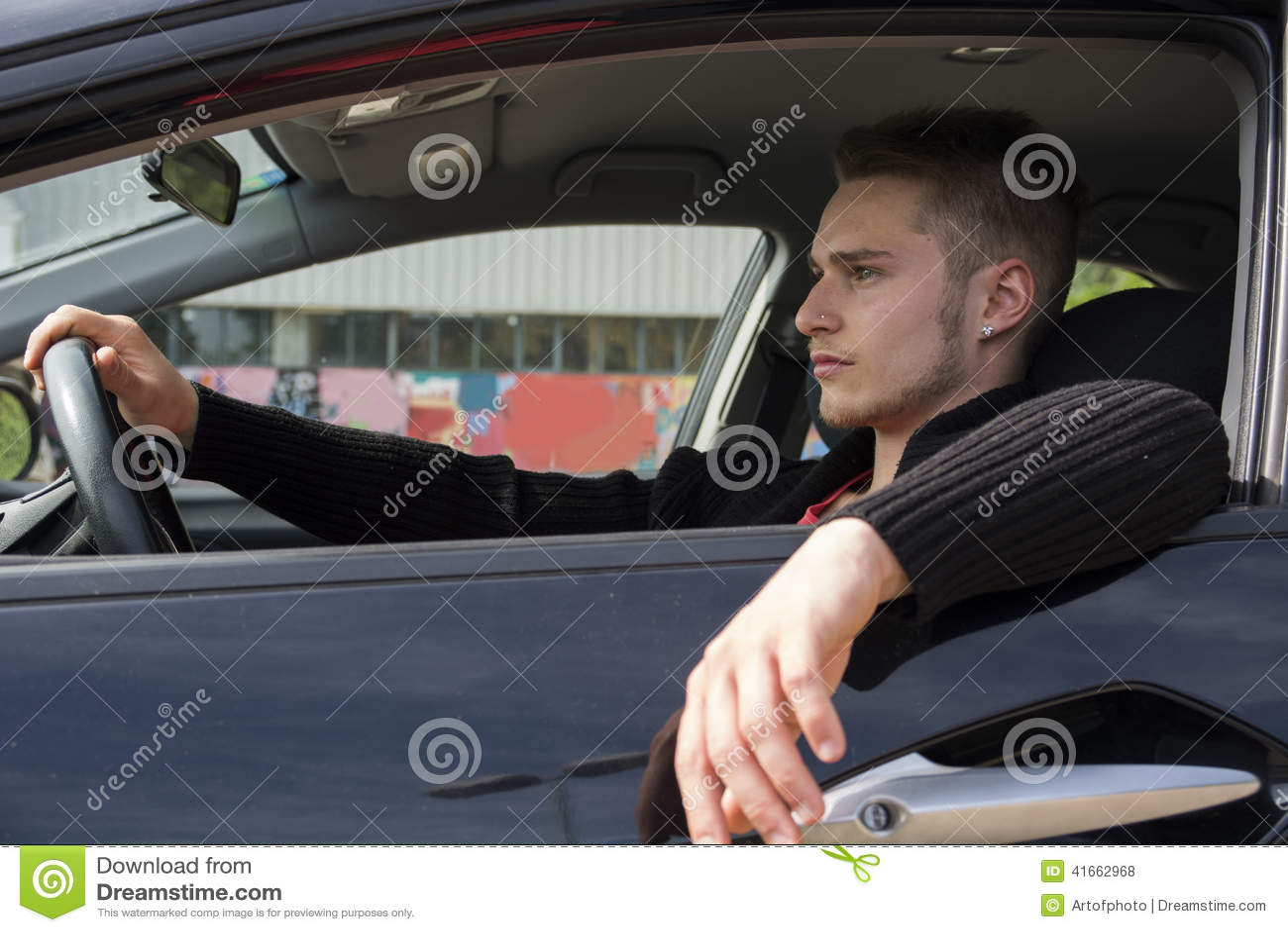 Красивый белокурый молодой человек сидя в его автомобиле