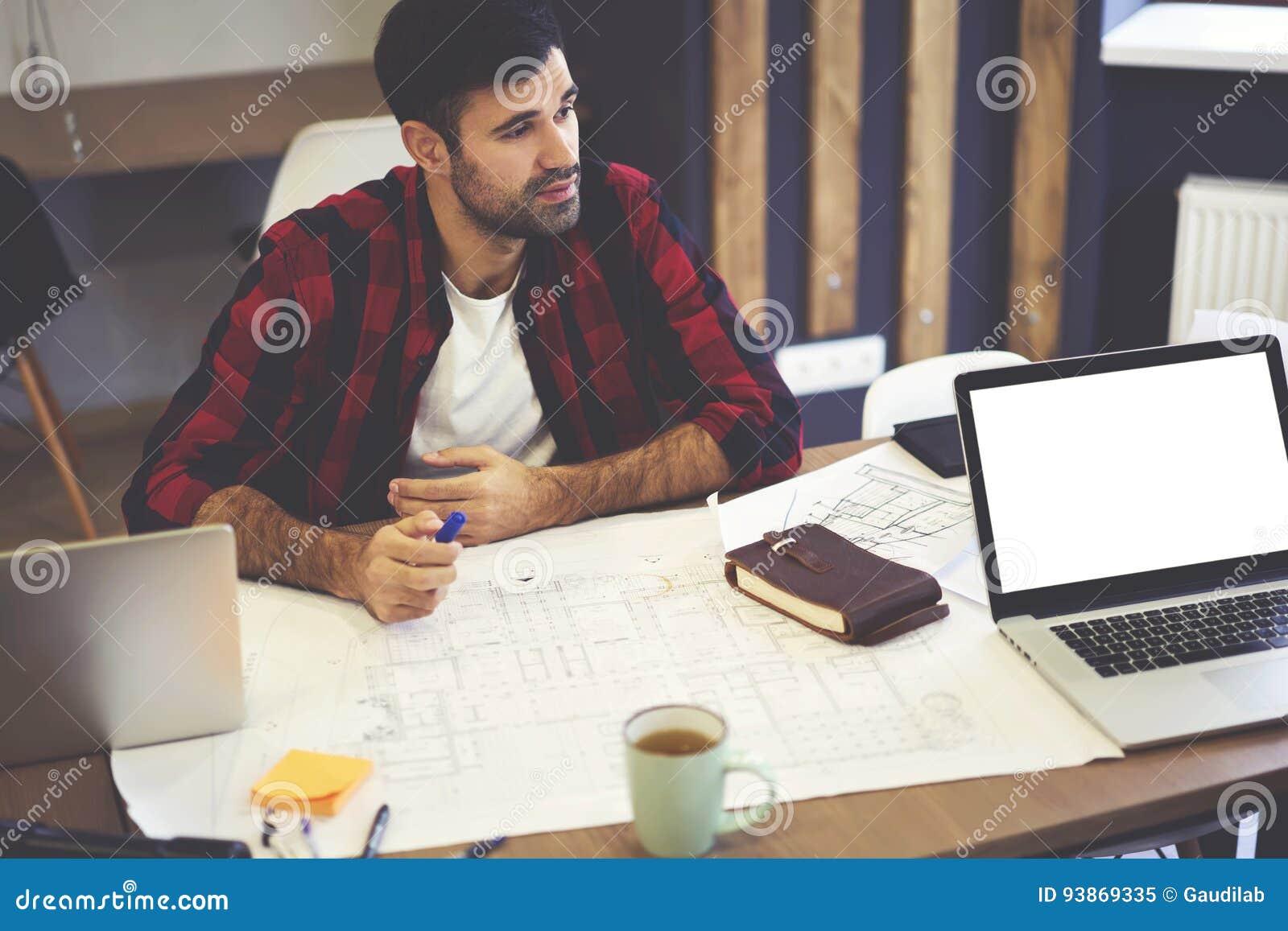 Красивый бородатый мужской инженер думая пока рисующ графические издержки
