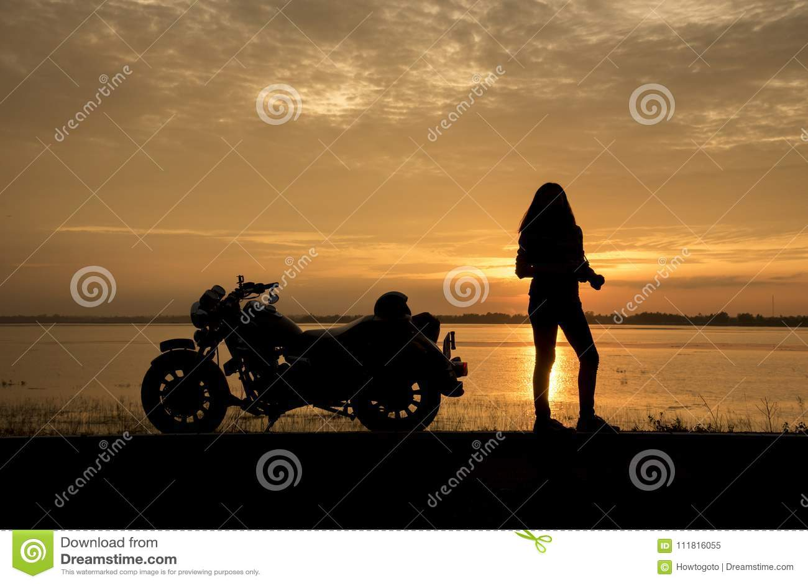 Красивый велосипедист женщины наслаждаясь заходом солнца, женским мотоциклом катания водитель мотоцилк путешествуя мир, ослабляя