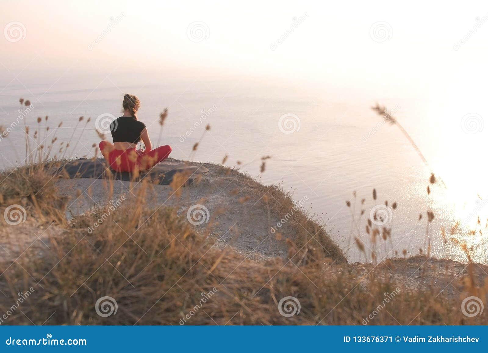 Красивый вид женщины делая йогу на горе с видом на море на заходе солнца задний взгляд