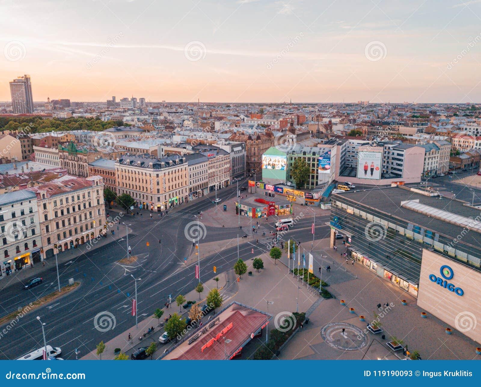 Красивый вид с воздуха городка Риги сверху во время захода солнца с башней с часами, старыми улицами города и городка