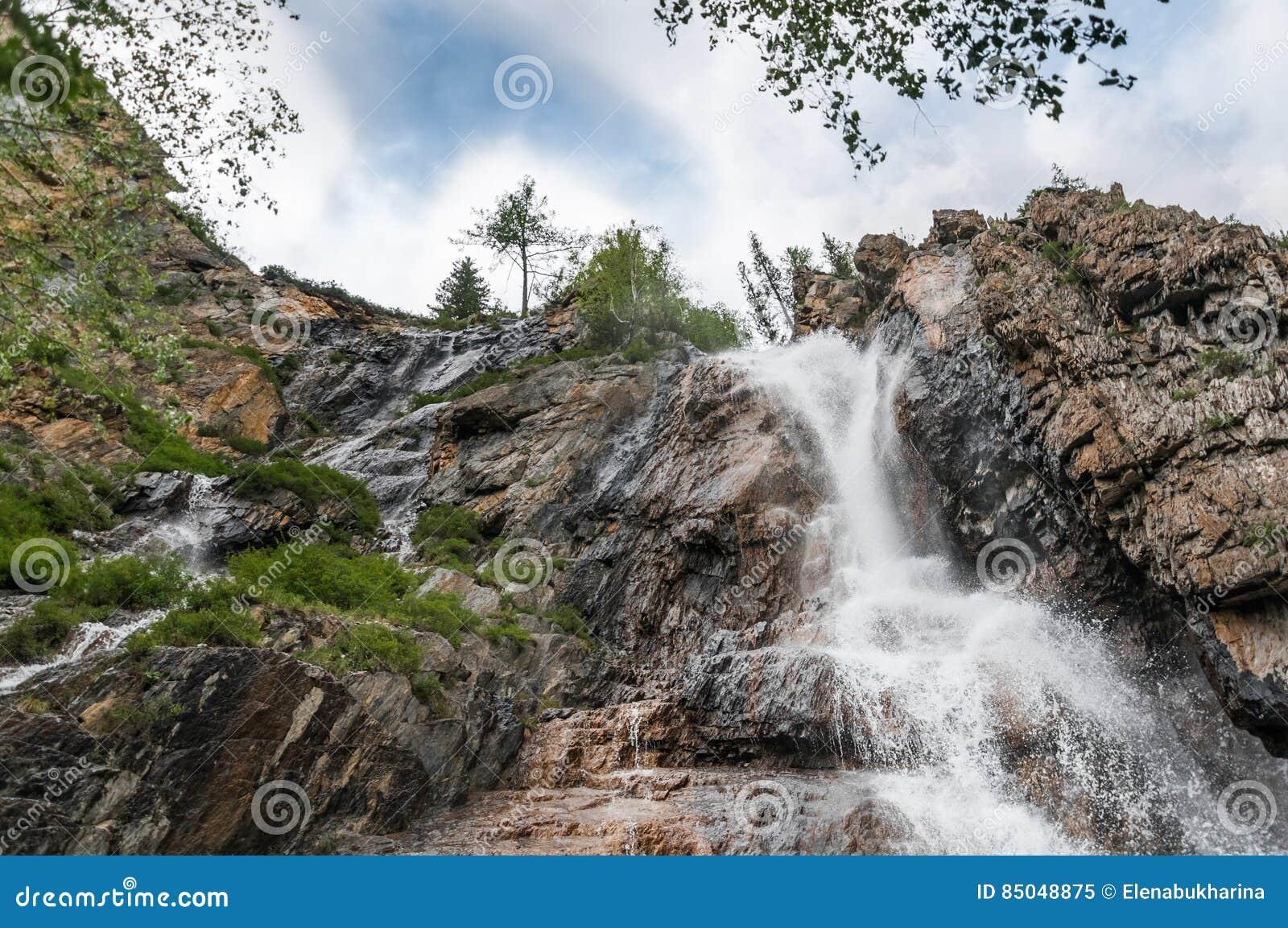 Красивый водопад на утесах в горах Altai