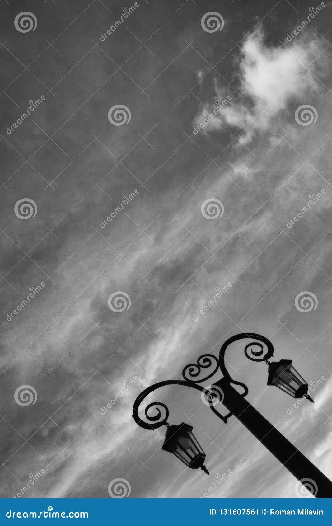 Красивый выкованный винтажный фонарик против неба черная белизна