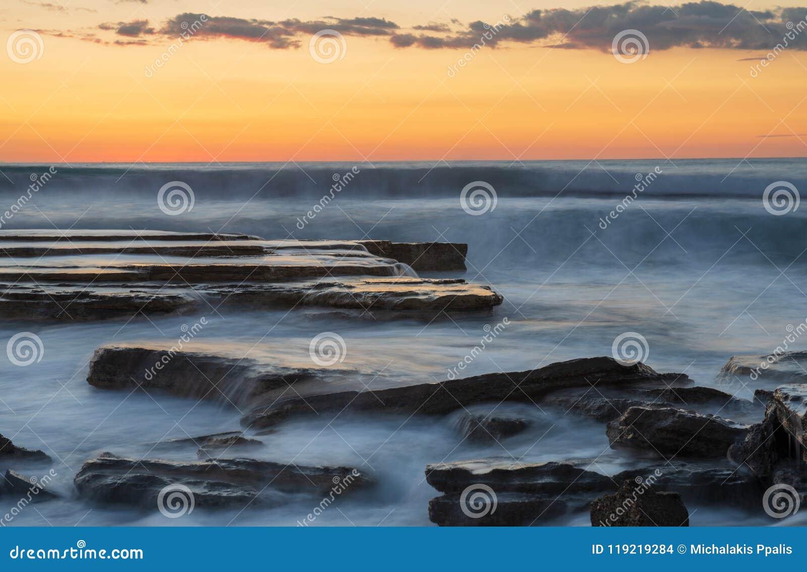 Красивый драматический заход солнца над скалистым побережьем