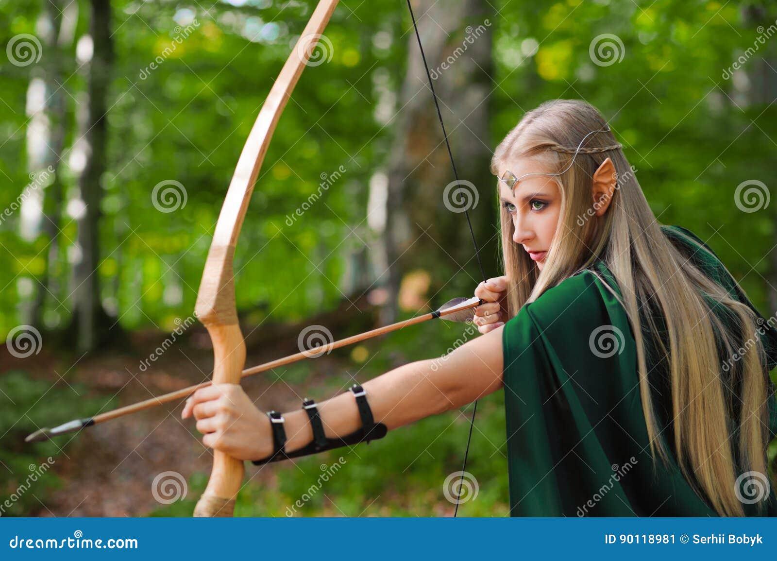 Красивый женский лучник эльфа в звероловстве леса с смычком