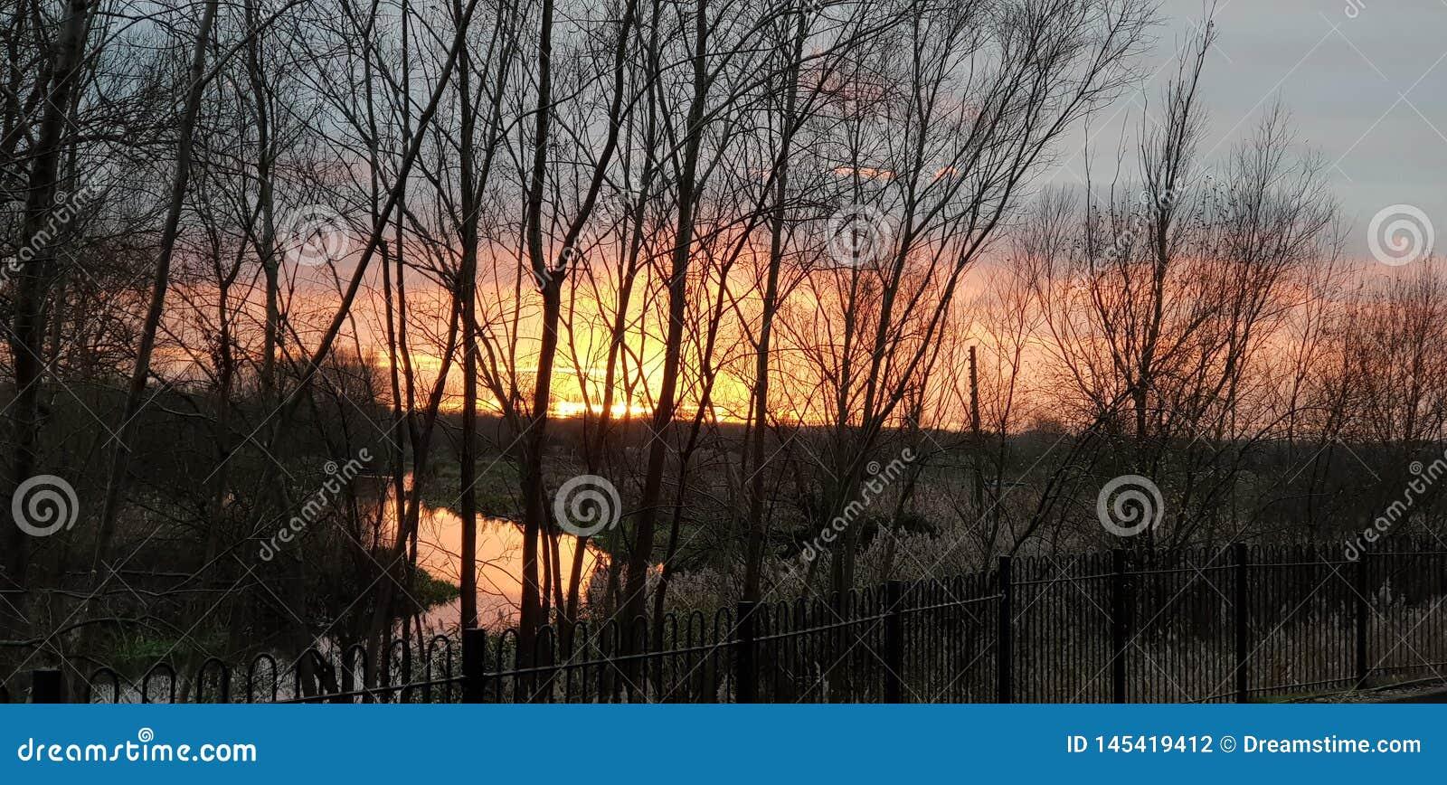 Красивый заход солнца в Olney Мильтон keynes над рекой Ouse с оранжевым красным и розовым небом