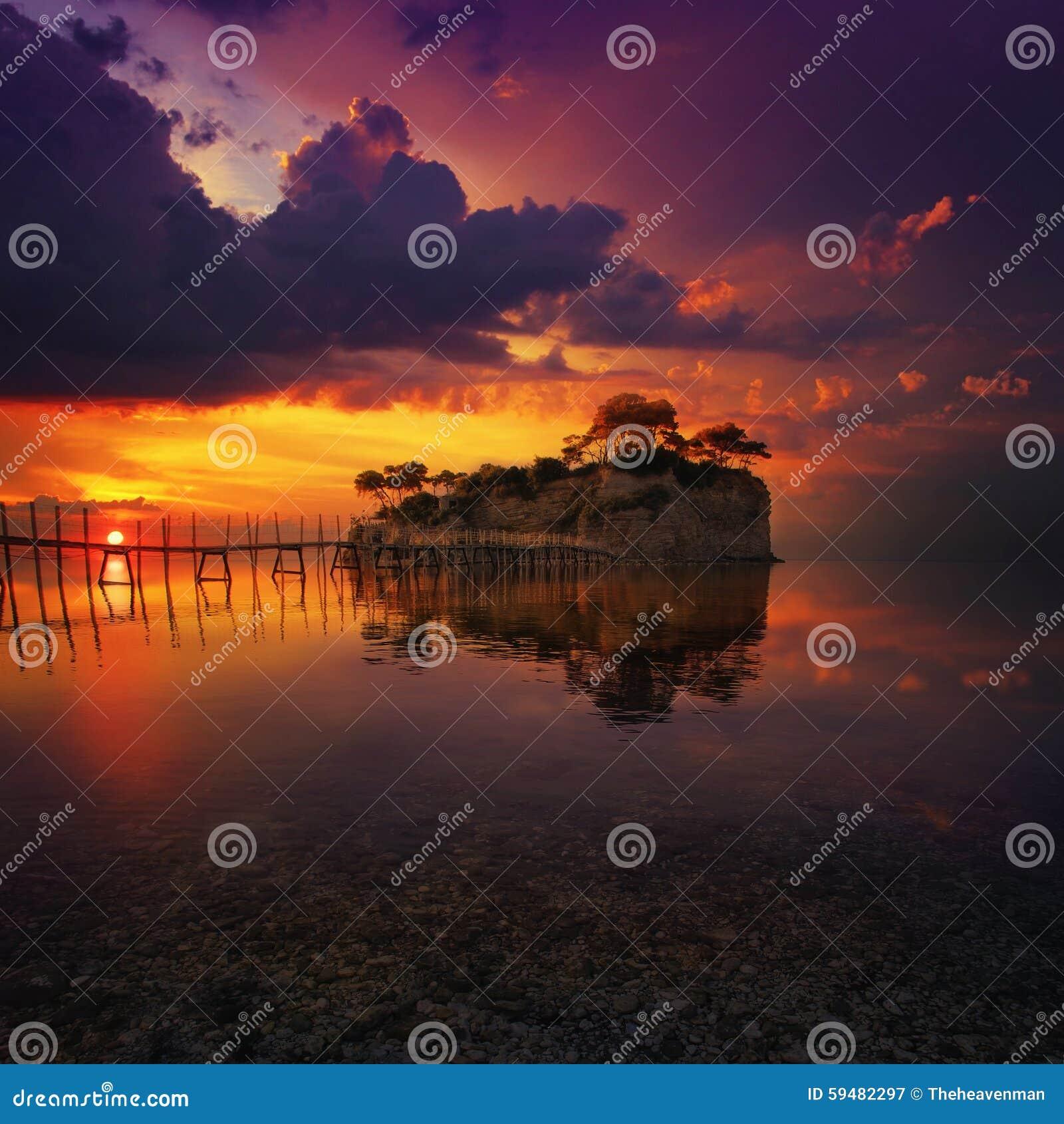 Красивый заход солнца с скалистым островом