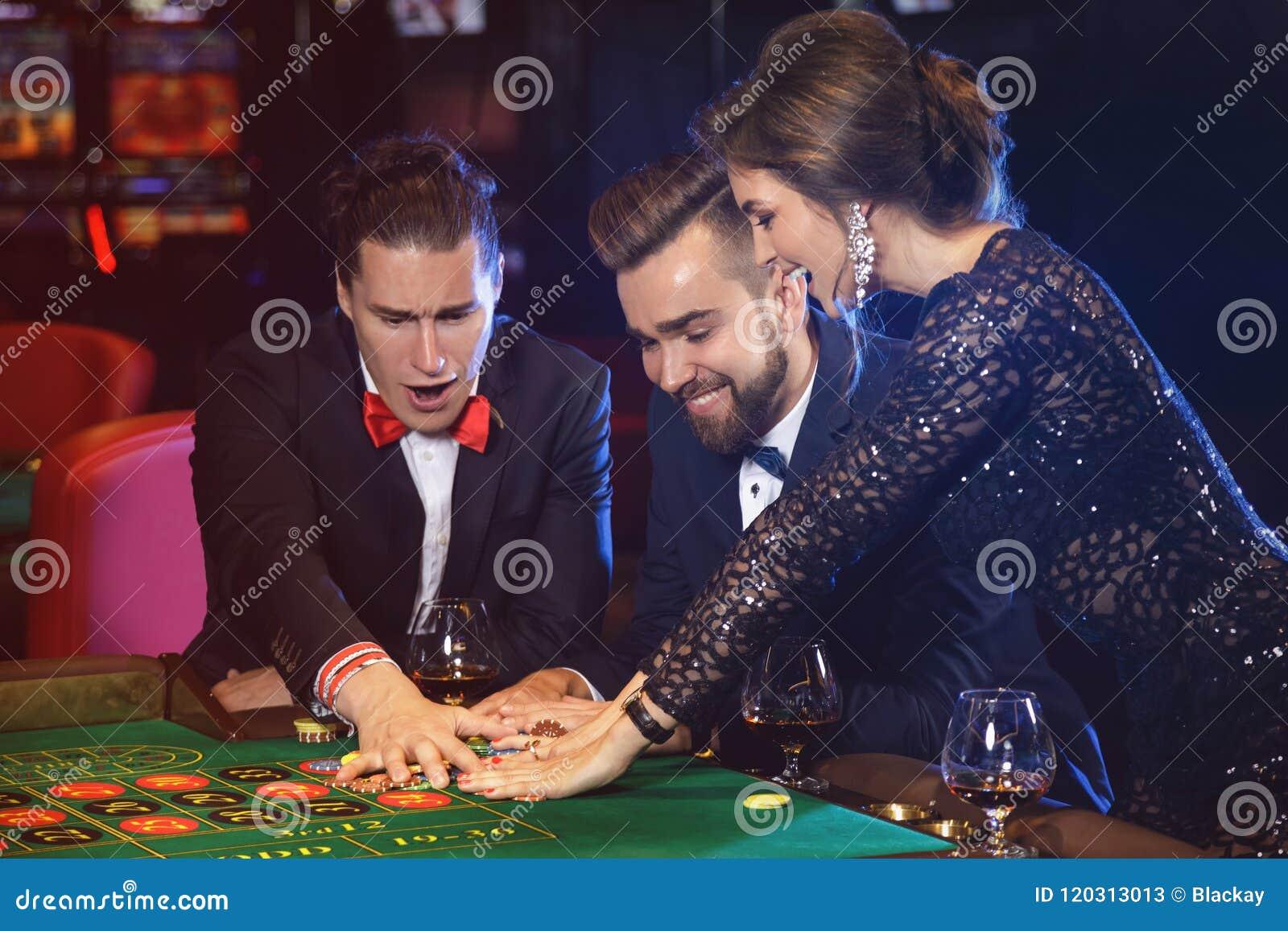 Красивый и богатый человек играя рулетку в казино