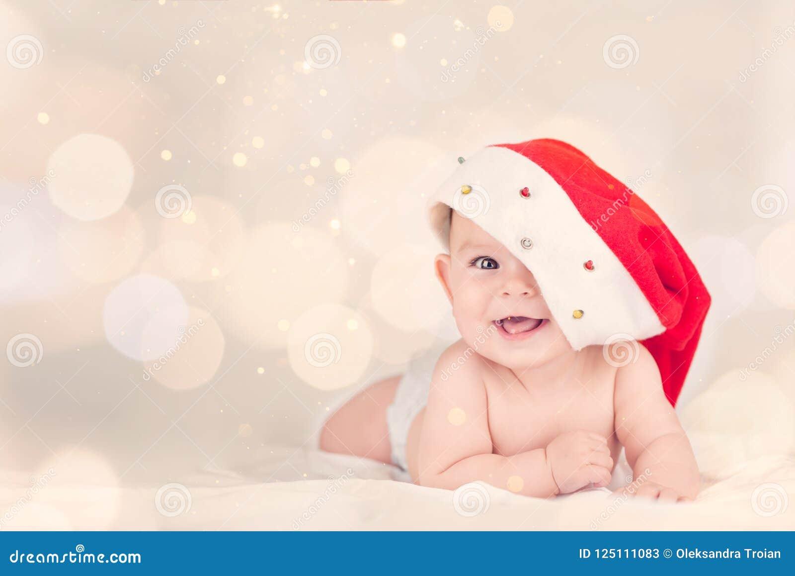 Красивый маленький младенец празднует младенца праздников ` s Нового Года рождества красная шляпа boken предпосылка
