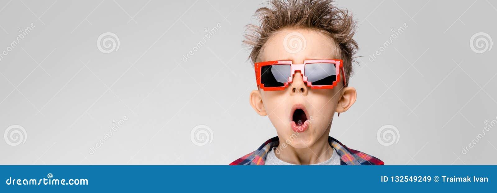 Красивый мальчик в рубашке шотландки, серой рубашке и джинсах стоит на серой предпосылке Солнечные очки мальчика нося Рыжеволосый