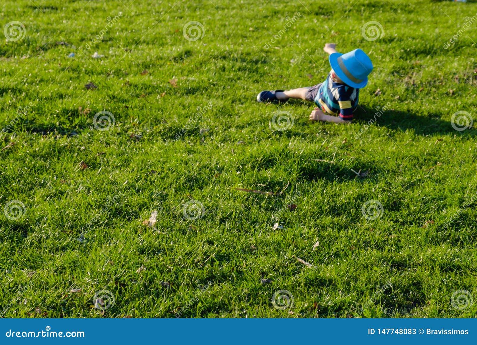 Красивый мальчик лежа на траве Немногое фантазер лежит в луге со шляпой Ребенок в природе вне города Беспечальные каникулы