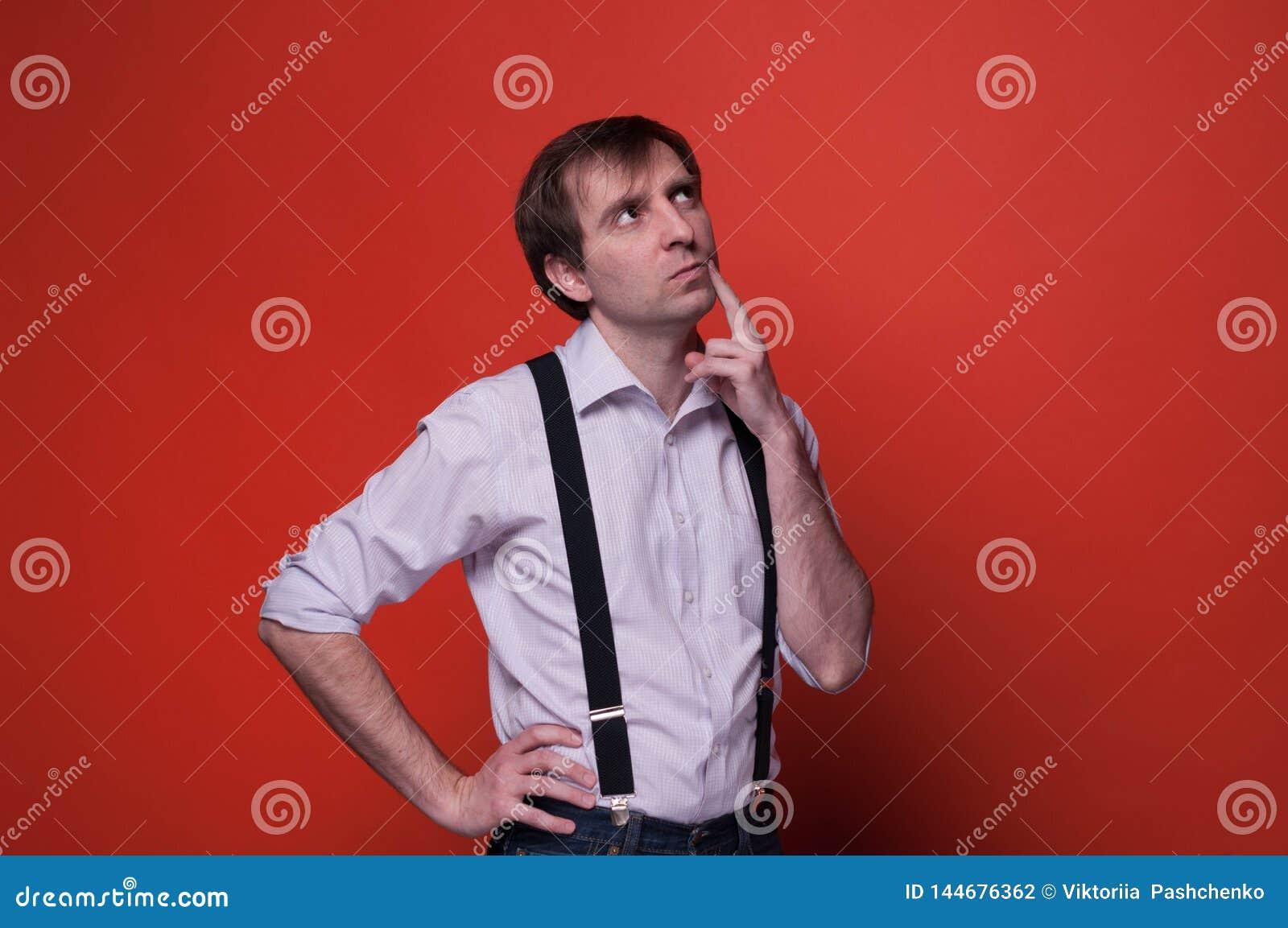Красивый мечтательный человек в рубашке и черном подтяжк