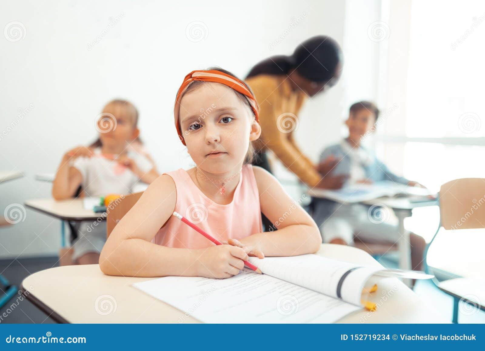Красивый милый карандаш удерживания девушки пока сидящ на столе
