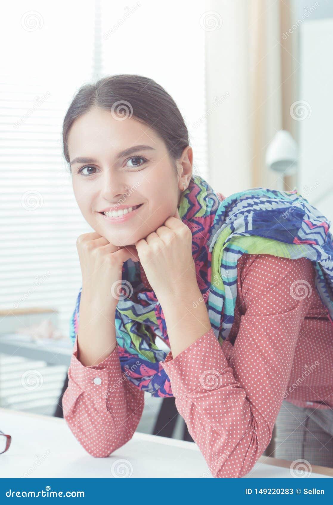 Красивый модельер сидя на столе в студии