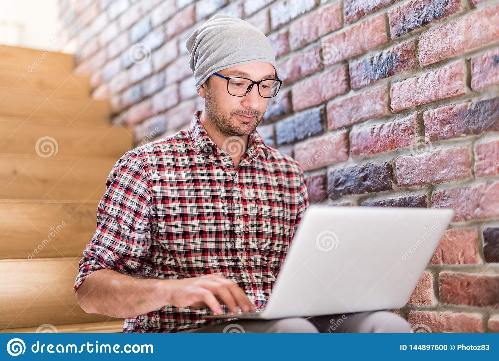 Красивый модный бизнесмен используя ноутбук пока сидящ на лестницах