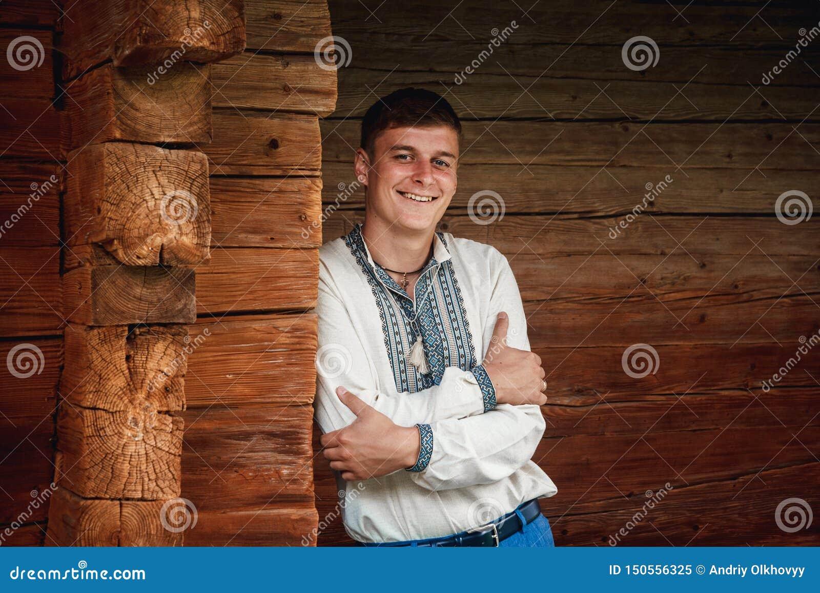 Красивый молодой парень в вышитой рубашке на предпосылке деревянного дома