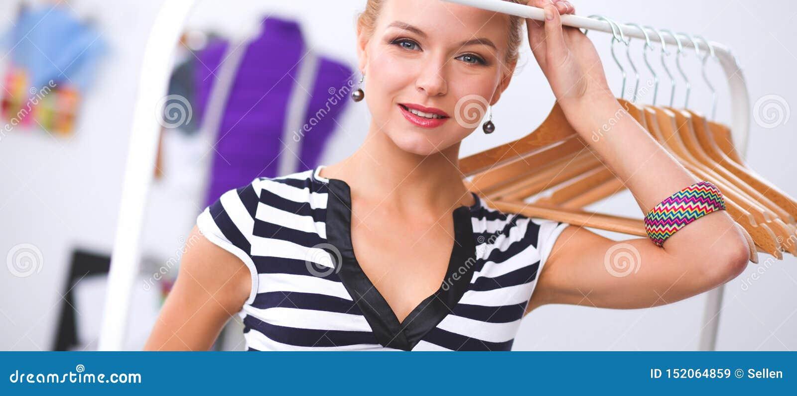Красивый молодой стилизатор около шкафа с вешалками