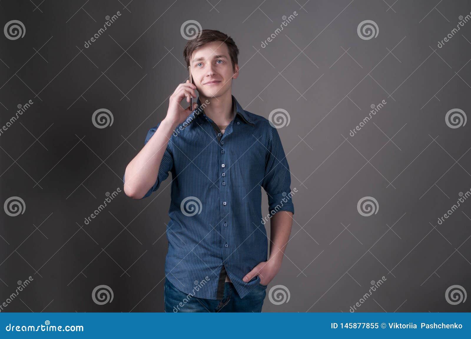 Красивый молодой человек говоря на смартфоне, усмехаясь и смотря прочь на серой предпосылке