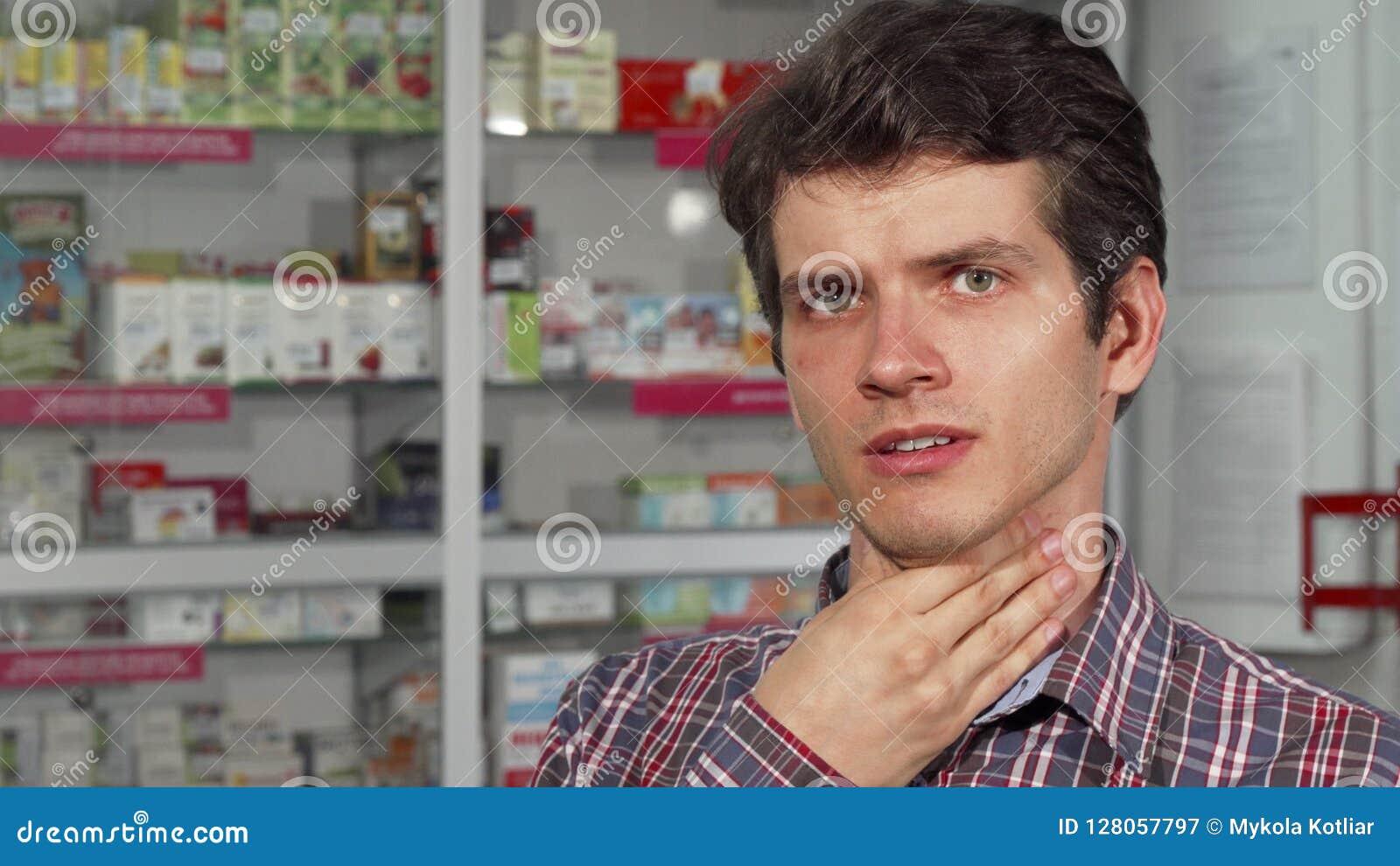 Красивый молодой человек кашляя имеющ боль в горле стоя на фармации