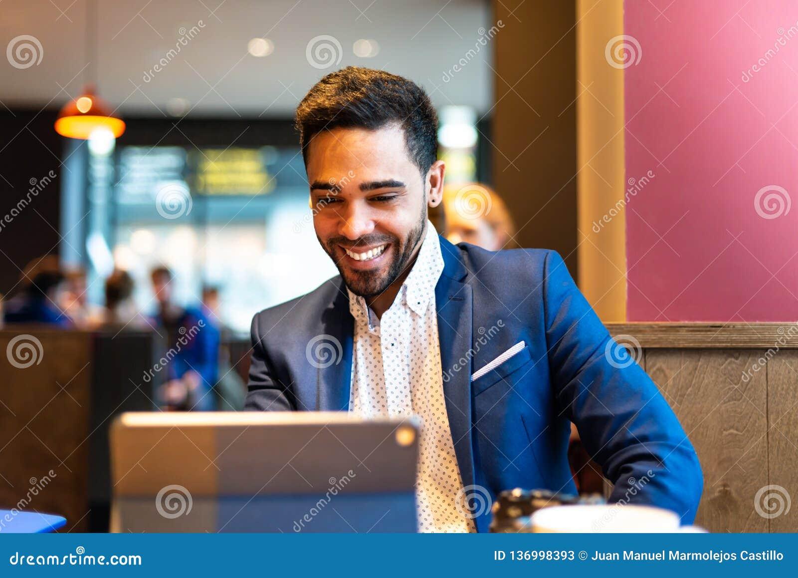 Красивый молодой человек на костюме используя ноутбук