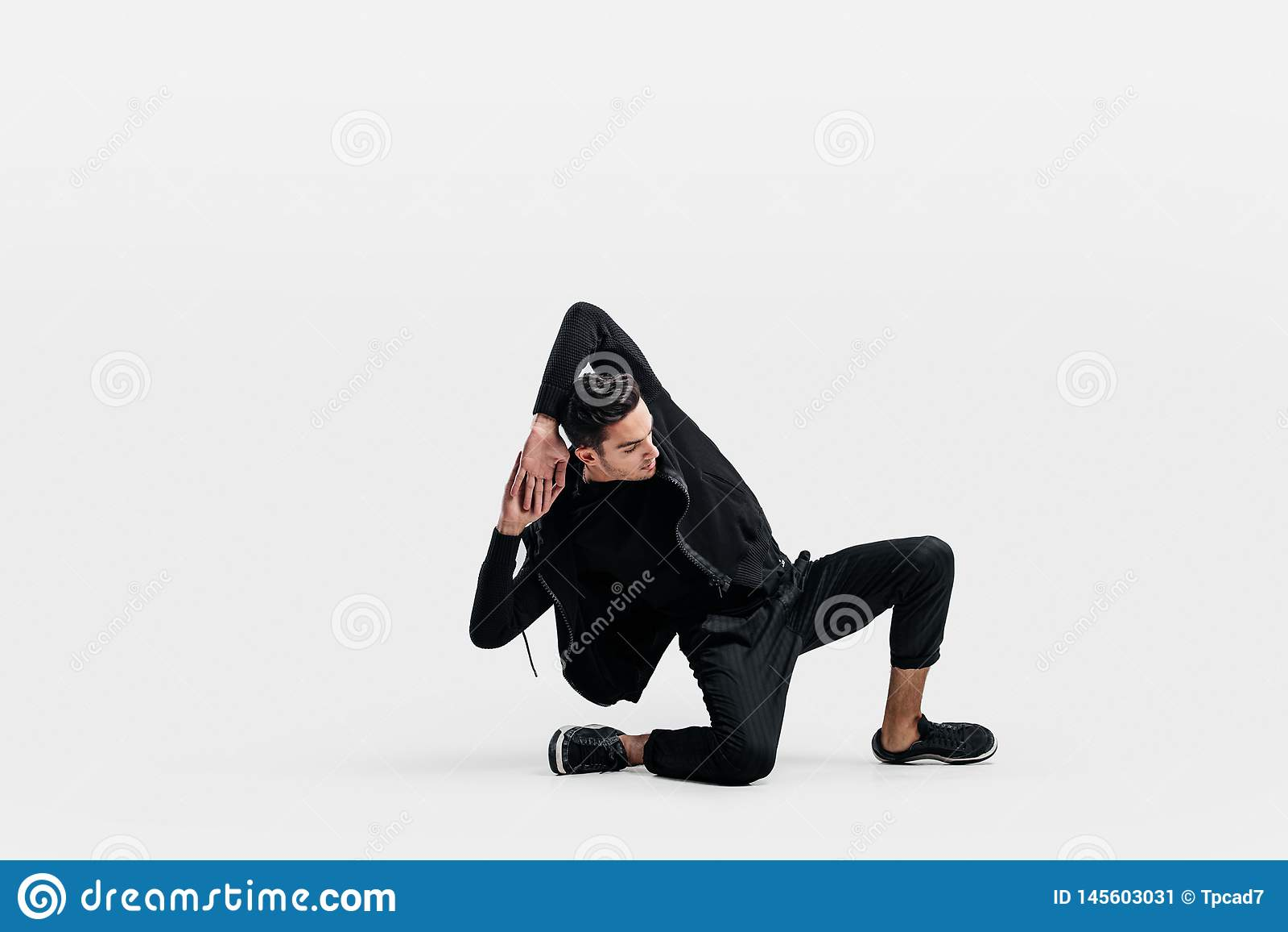 Красивый молодой человек нося черную фуфайку и черные брюки танцует breakdance делая танцуя движения на поле