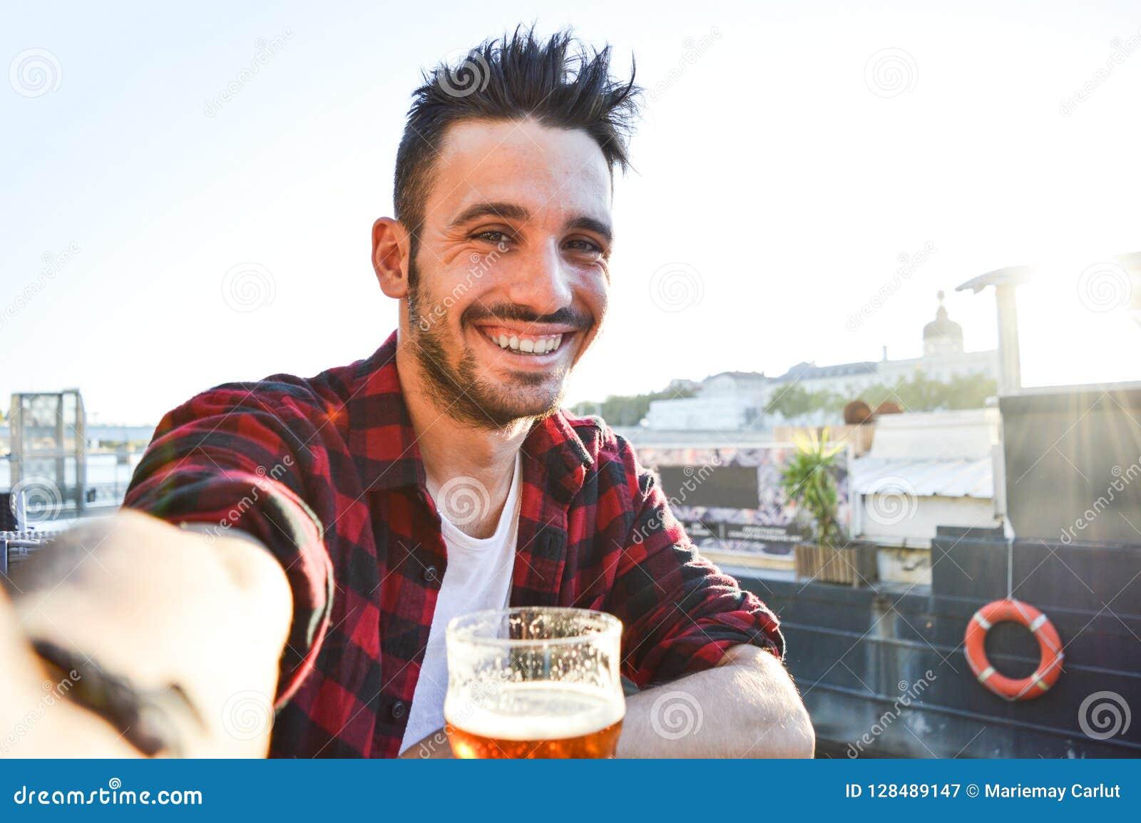 Красивый молодой человек принимая selfie выпивая пиво на баре
