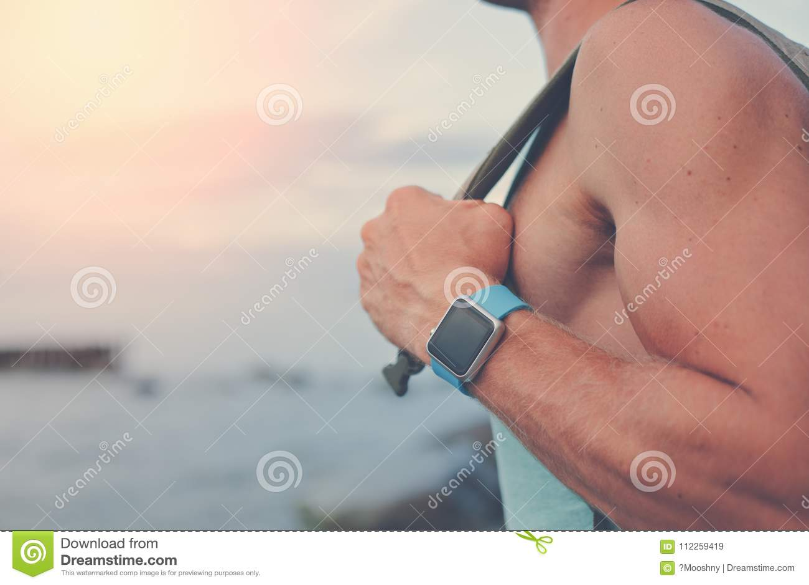 Красивый молодой человек при рюкзак нося умные вахты около океана