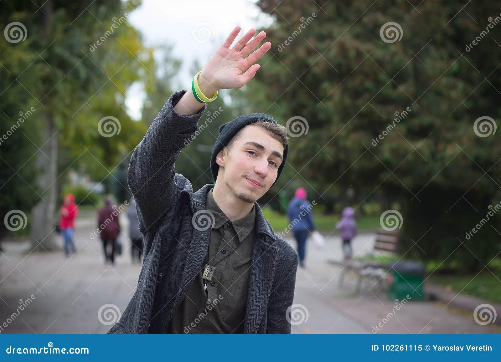 Красивый молодой человек развевая к кто-то, идущ, улица