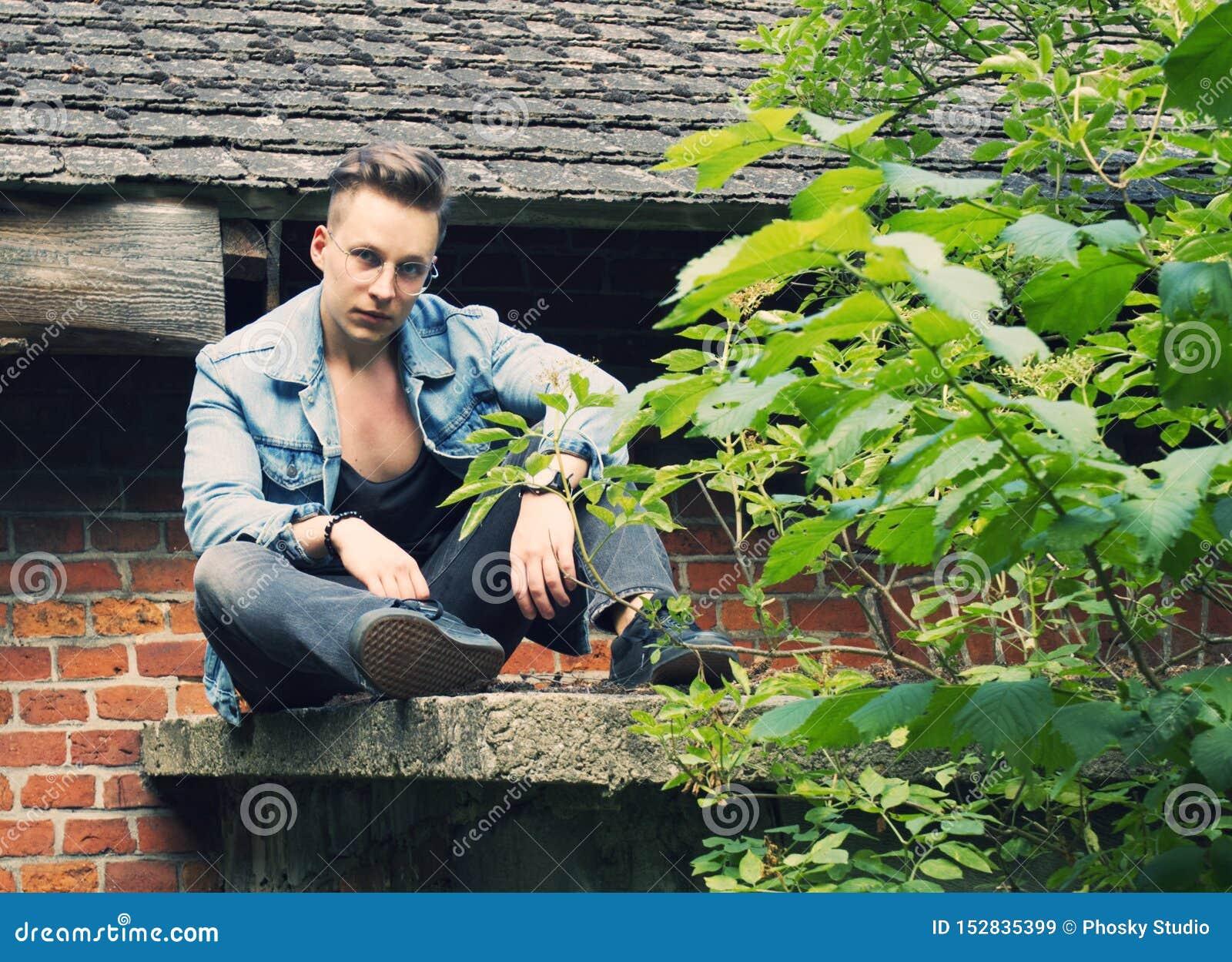 Красивый молодой человек сидя на крыше