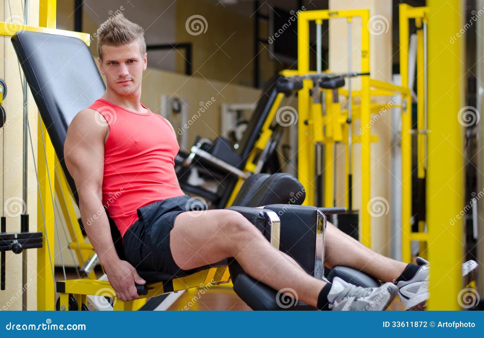 Красивый молодой человек разрабатывая на оборудовании спортзала