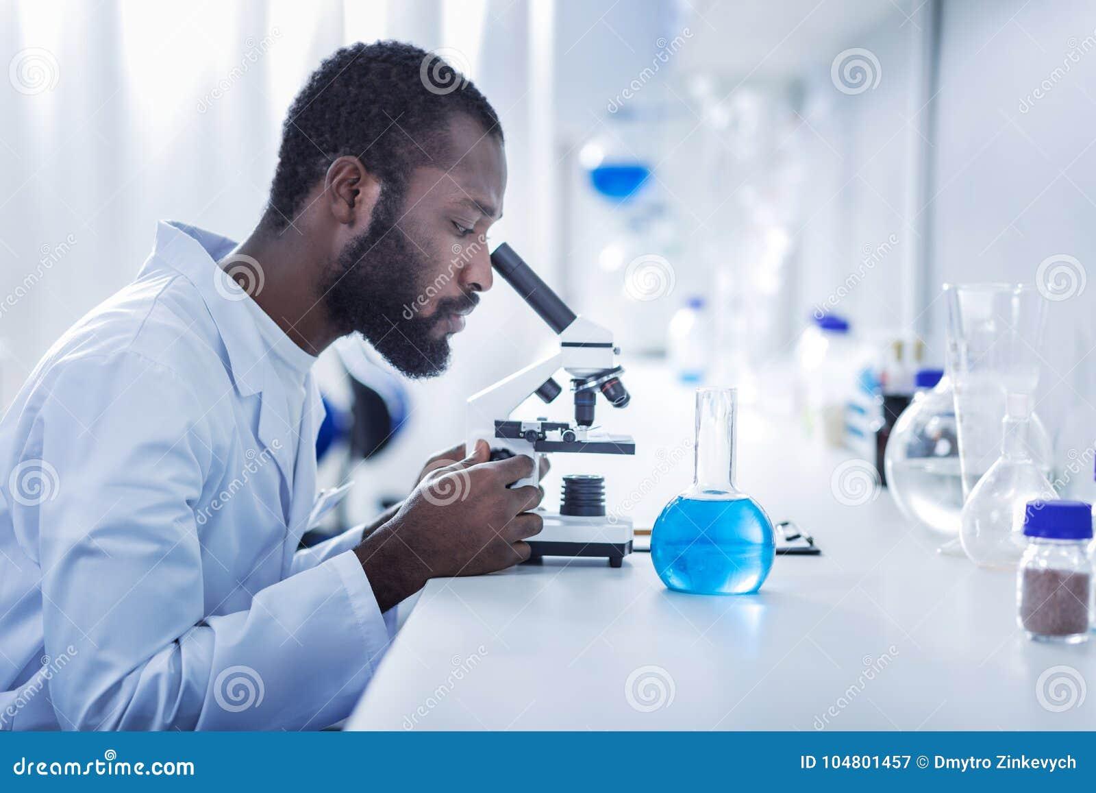 Красивый мужской ученый смотря в микроскоп