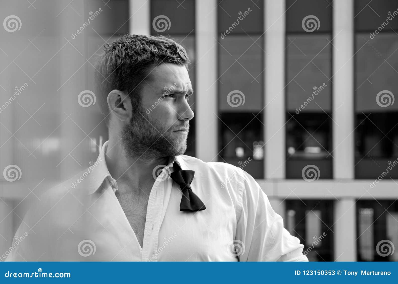 Красивый первоклассный человек с unbuttoned рубашкой и свободным bowtie стоит на балконе гостиницы с фоном sckyscraper