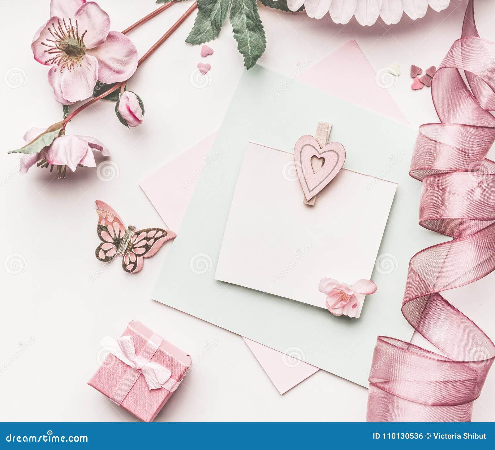 Красивый план пастельного пинка с украшением цветков, лентой, сердцами и насмешкой карточки вверх на белой предпосылке стола, взг