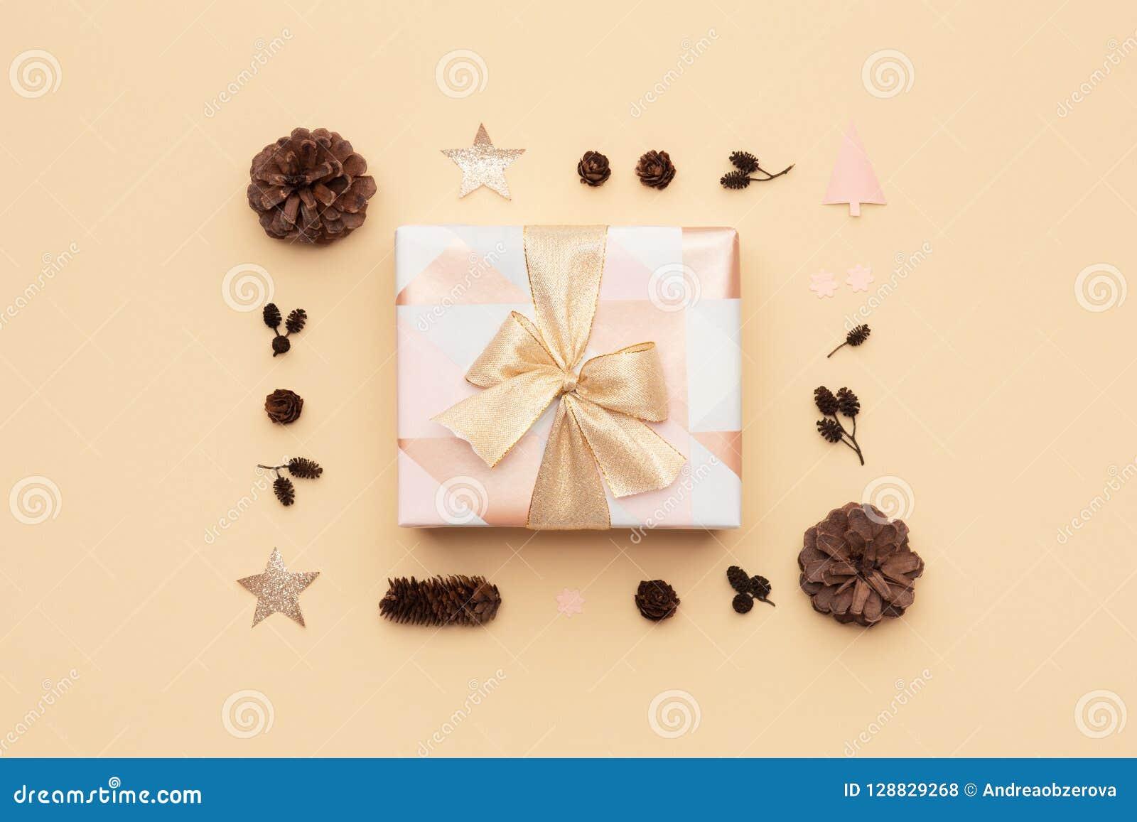 Красивый подарок рождества украшенный при смычок ленты изолированный на бежевой предпосылке Пинк и обернутая золотом коробка xmas