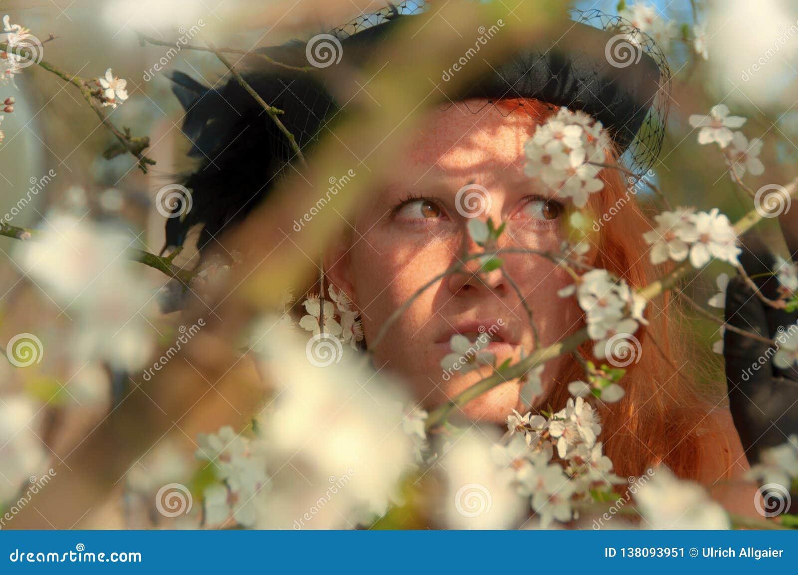 Красивый портрет конца-вверх молодой элегантной рыжеволосой курчавой женщины в дереве с белыми цветениями вишневого дерева яблони