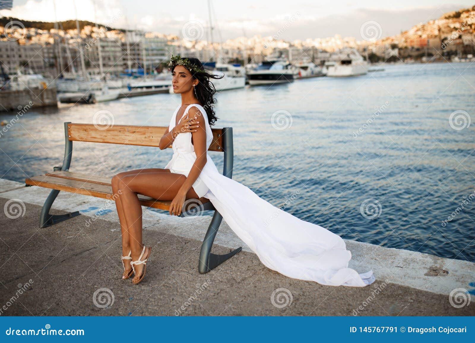 Красивый портрет молодой женщины брюнета представляет чувственное в белом платье на стенде, за Средиземным морем в Греции