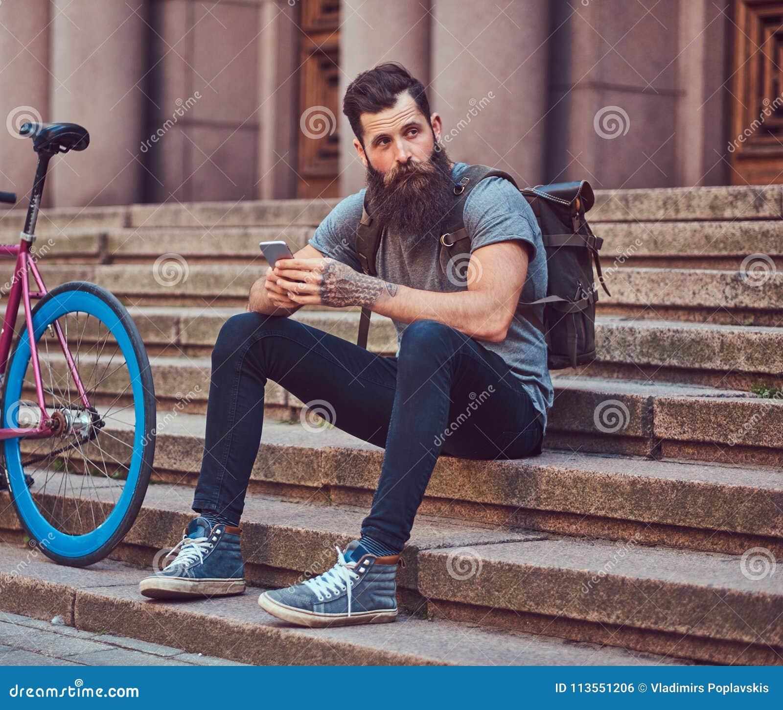 Красивый путешественник битника с стильной бородой и татуировка на его оружиях одели в вскользь одеждах, сидя на шагах