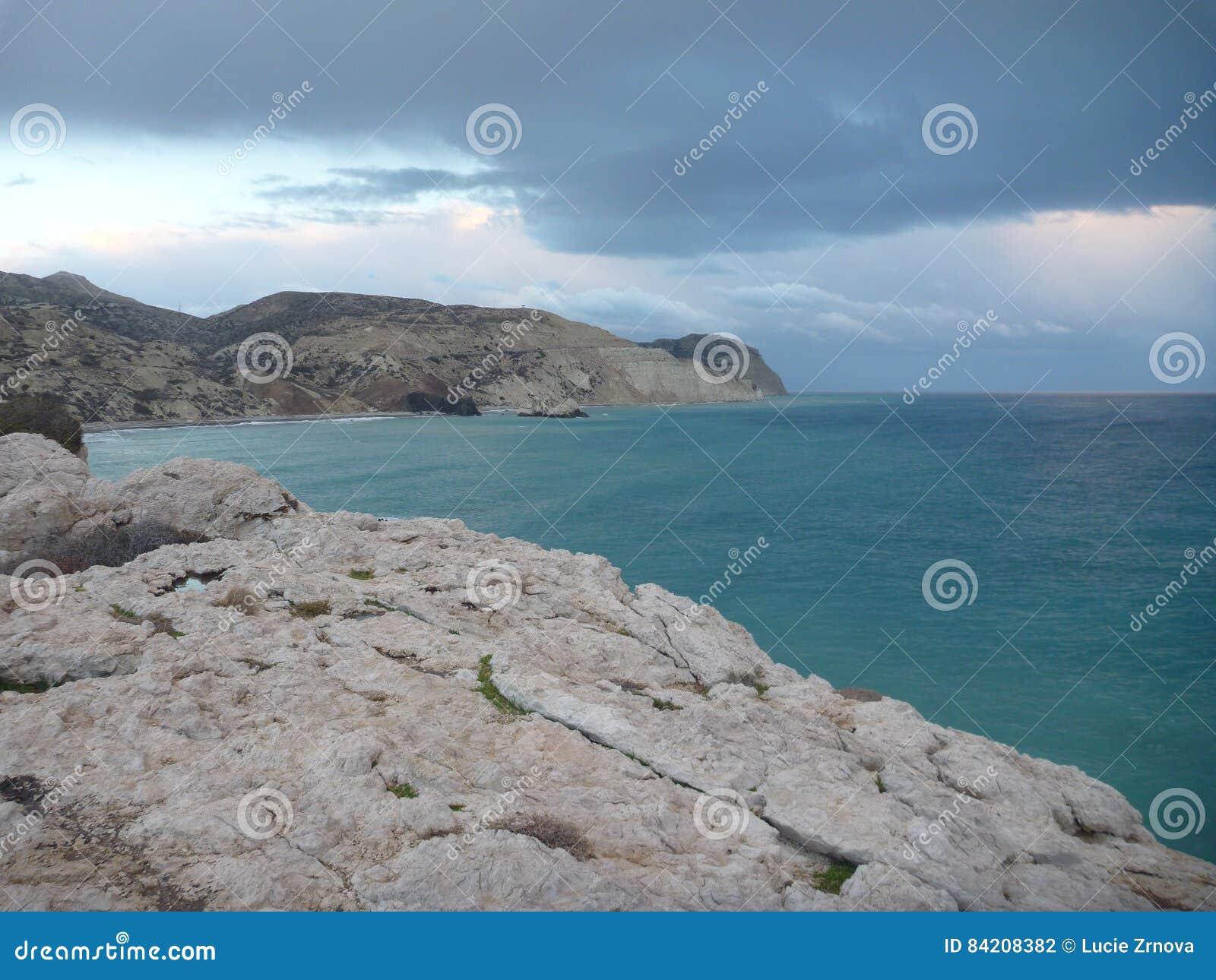 Красивый романтичный заход солнца на скалистом seashore