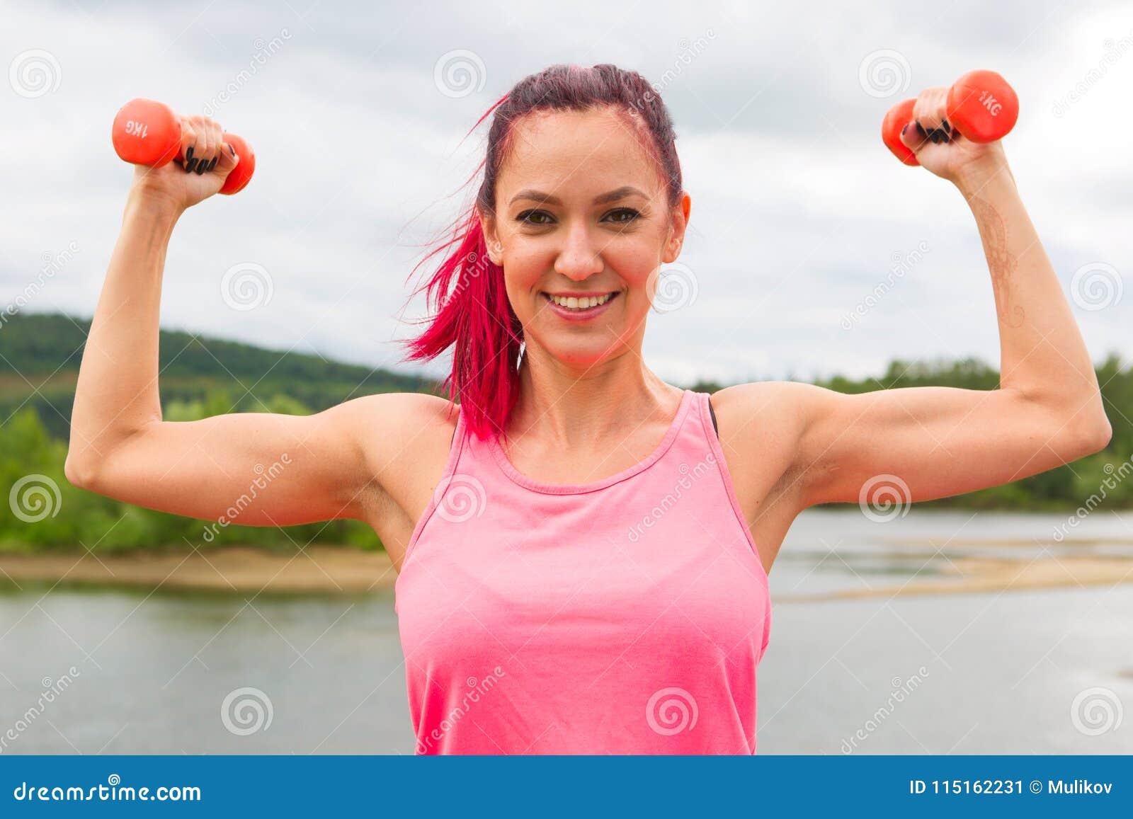 Красивый спортсмен девушки представляет работать с малой гантелью весов внутри outdoors