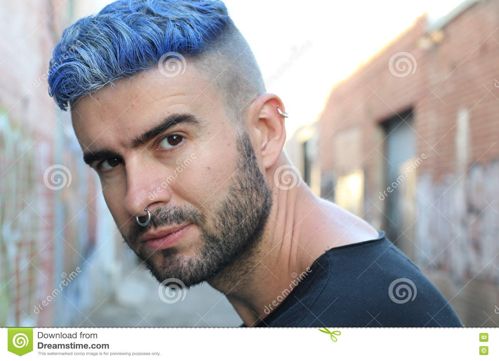 Красивый стильный молодой человек с искусственно покрашенными покрашенными синью стилем причёсок, бородой и прошивками волос подн