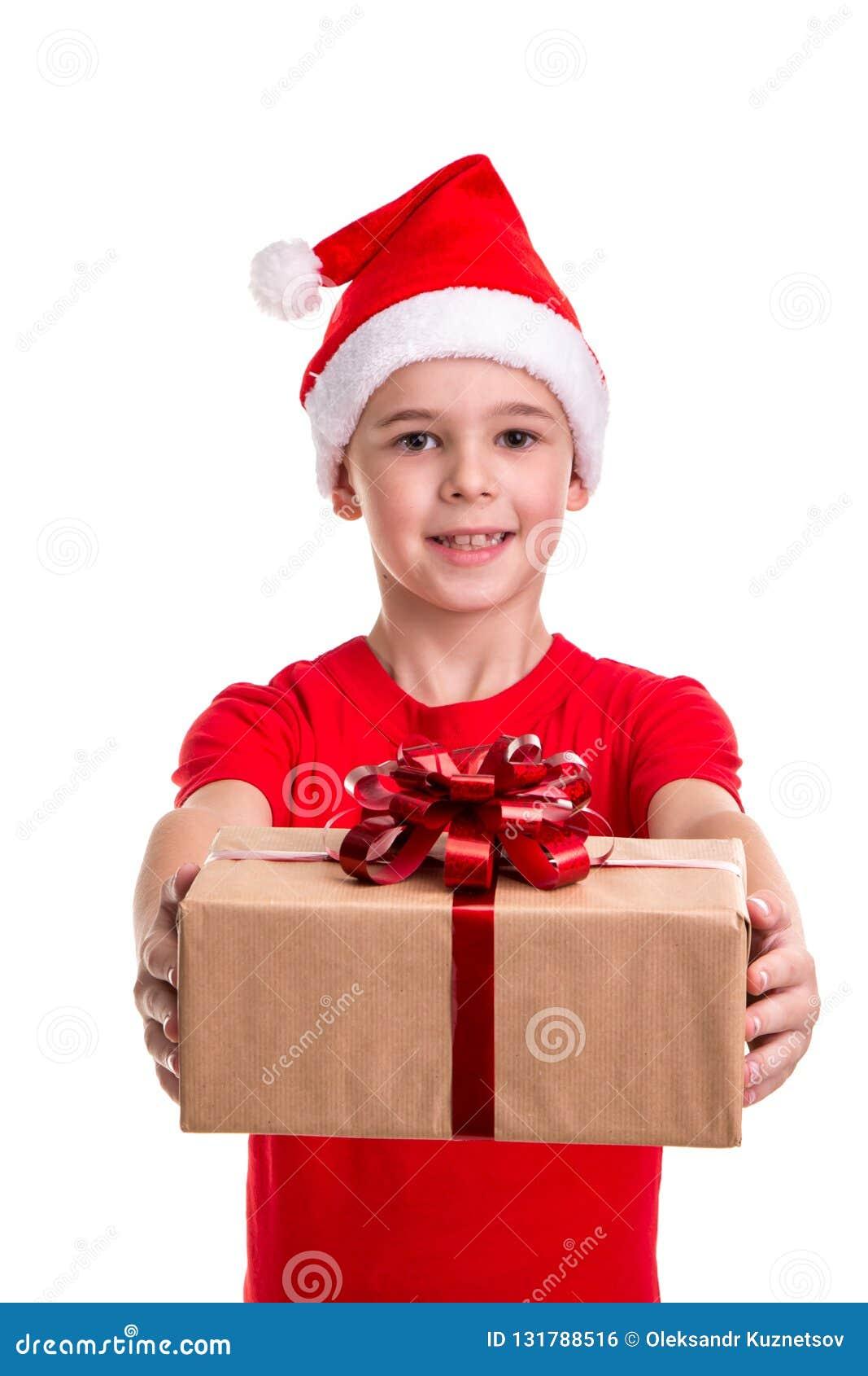 Красивый счастливый мальчик, шляпа santa на его голове, держа вне подарочную коробку Концепция: рождество или С Новым Годом! праз