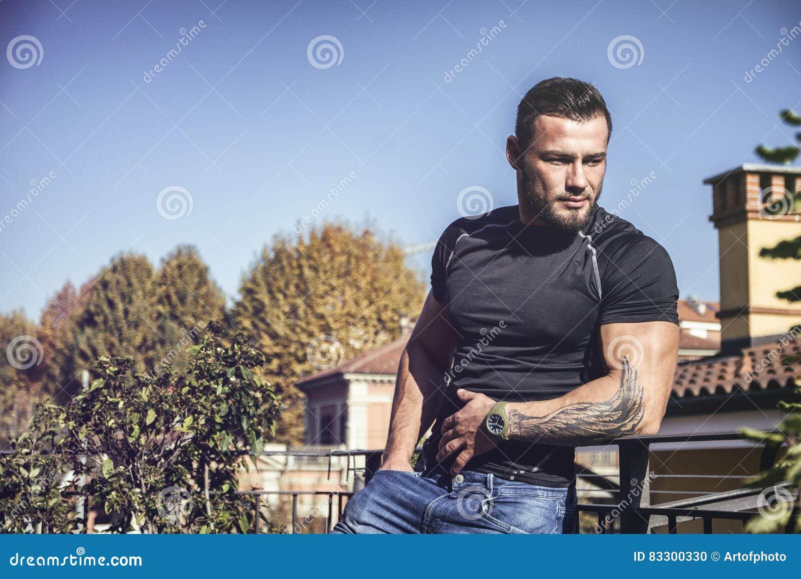 Красивый темный с волосами молодой человек смотря вне на взгляде