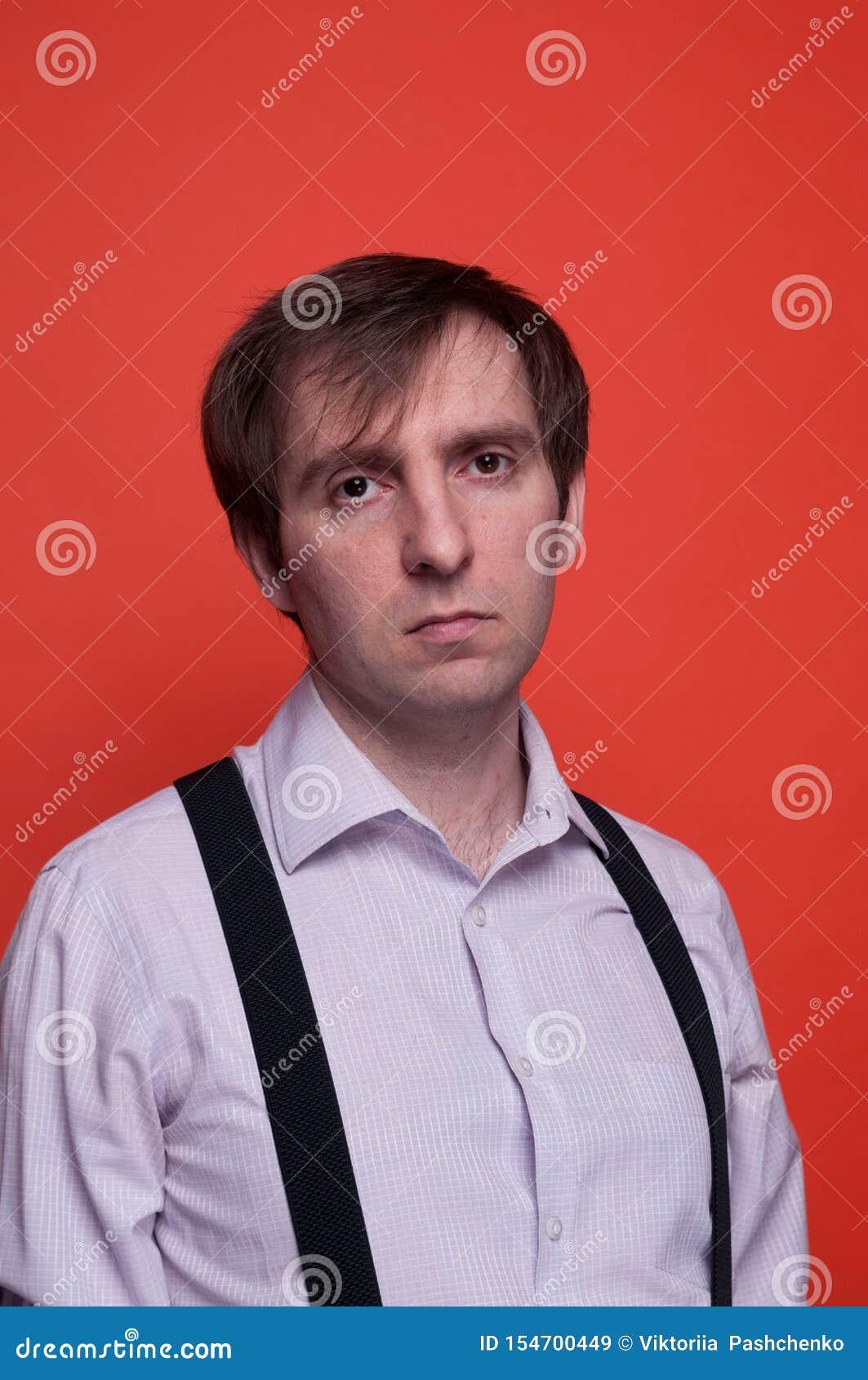 Красивый уверенный человек в розовой рубашке и черном подтяжк смотря камеру на оранжевой предпосылке
