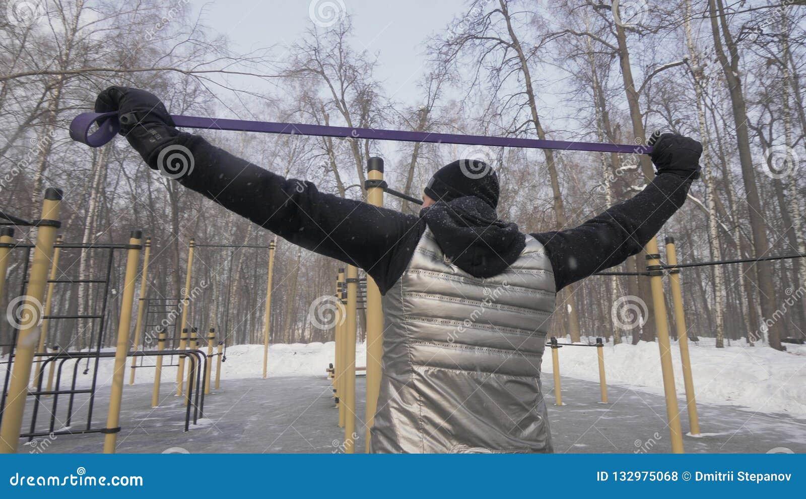 Красивый человек делая тренировку разминки с детандером фитнеса на земле спорт